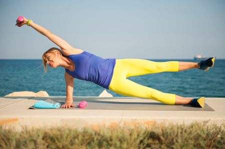 Young athletic woman exercising outdoors: side plank with dumbbells for total body strength Reklamní fotografie