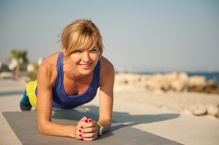 Young athletic woman exercising outdoors: plank for total body strength Stock Photo