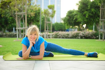 屋外で運動運動女性: 柔軟性のためのクールなダウンとストレッチ 写真素材