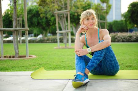 公園内運動マットの上に座っていた運動女性: トレーニングの準備ができて