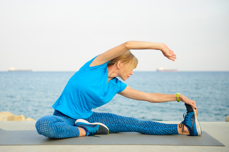 Young athletic woman exercising outdoors: cool down and stretch for flexibility Stock Photo