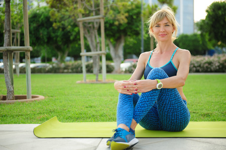 Young athletic woman sitting on the exercising mat in a park: ready for workout Stock Photo