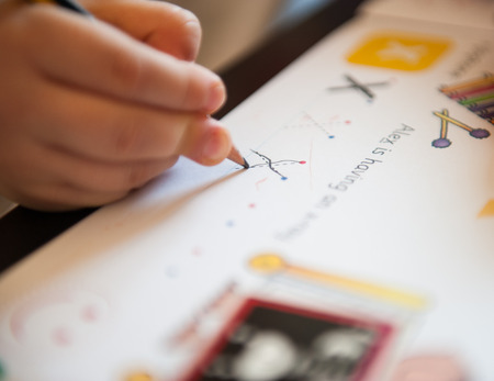 3-year-old child is learning to write by tracing alphabet letters - letter x