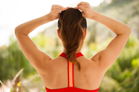 Young athletic woman exercising on verandah: preparing for workout Stock Photo