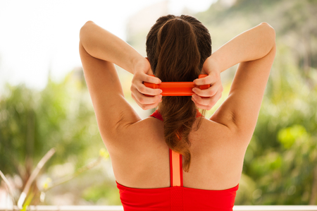Young athletic woman exercising on verandah: tricep extensions for upper body strength