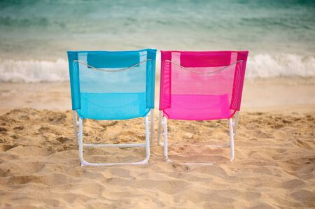 2 foldable chairs on the beach
