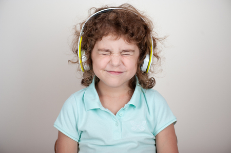 Young child in headphones, closed her eyes tightly