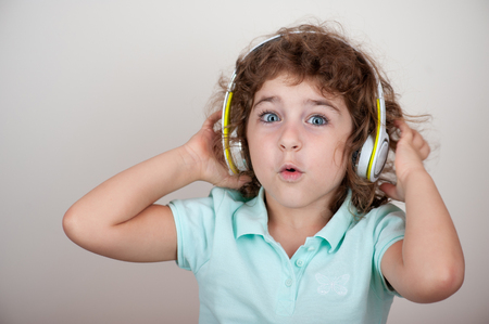 Young child in headphones, enjoying sound, holding headphones with her hands