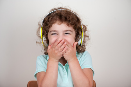 Young child in headphones, laughing, covered her mouth with hands, funny sound Banco de Imagens