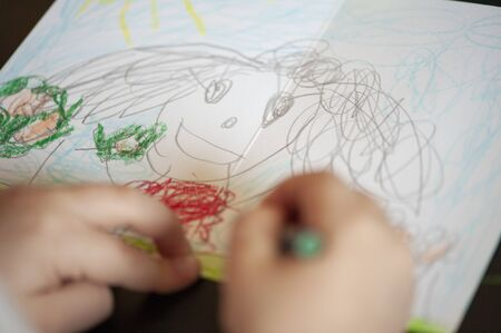 Child is drawing a card for her friend - portrait of a friend
