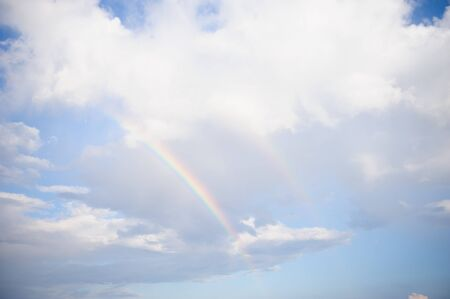 Sky with clouds and rainbow after rain