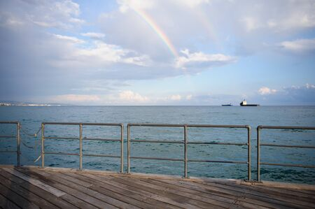 Marine landscape with stormy sky and a rainbow after rain Stock Photo