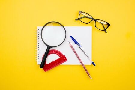 School and office supplies flay lay on colorful yellow background. Magnifier, protractor, sketch book, pencil, pen and glasses layout top view. Back to school concept. Template for web. Stock photo.