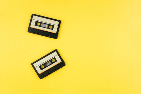 Retro audio cassette tape flat lay on colorful yellow background top view with copy space. Creative fashion design in minimal 80-s style. Music, radio, dj concept. Web banner template. Stock photo.