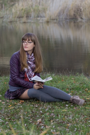 young girl reading a book at the lake photo