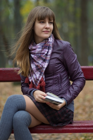 young girl with a book on a bench photo