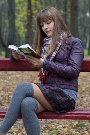leg warmers: young girl reading a book on a bench Stock Photo