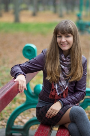 young girl sitting on a bench in the park photo