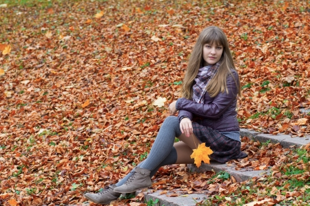 girl on the steps in the yellow leaves Stock Photo