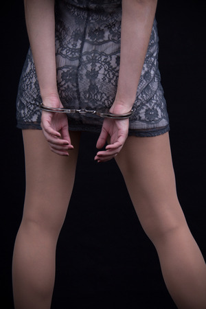 Girl in handcuffs on black background photo