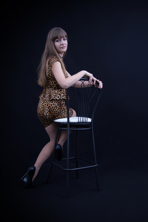 Cute girl in leopard dress on a chair photo
