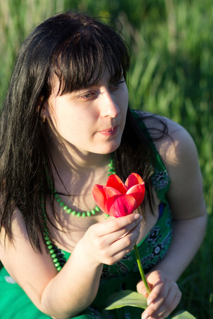 Beautiful girl with a flower in nature photo