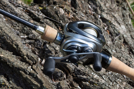Modern fishing reel close-up on a tree trunk photo