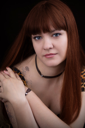 Portrait of red-haired girl with a rose tattoo photo