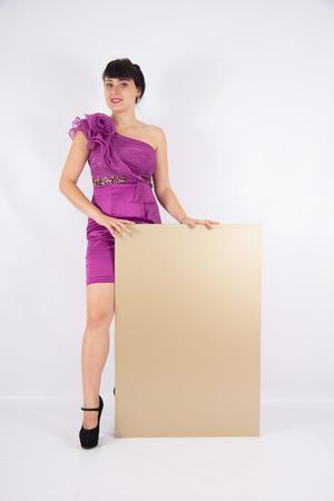 Beautiful girl in a short dress with billboard photo