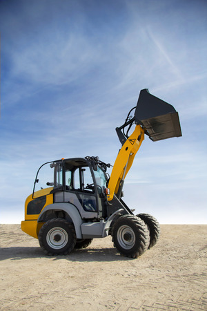 technologically: Yellow tractor with the lifted bucket on a background of blue sky Stock Photo