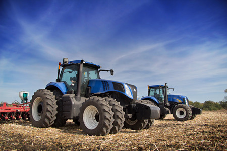 Two blue tractor with drills in the field under blue sky Stockfoto