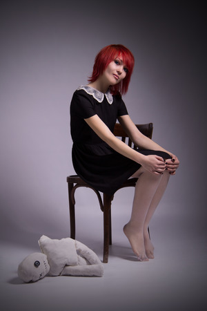 body piercing: Red-haired girl, dress with lace collar, rag doll sitting on a chair, gradient background, blue eyes, vintage image, vertical photo, body piercing on her face, informal appearance. Stock Photo