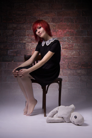 body piercing: Red-haired girl, dress with lace collar, rag doll sitting on a chair, brick wall, blue eyes, vintage image, vertical photo, body piercing on her face, informal appearance.