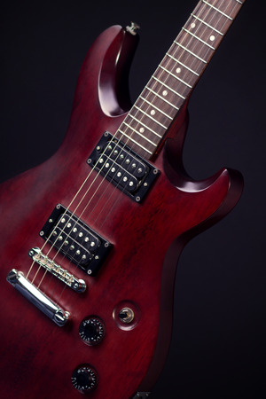 stringed: Electric guitar mahogany, dark background, vertical image, a stringed musical instrument, electronic control bodies, six-string guitar, body of the guitar, tuning and adjustment.