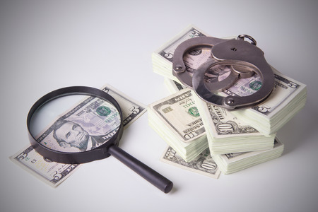capital punishment: Finance and Law, economic crime, the punishment of the offender, pack of dollars, steel handcuffs, horizontal image, DSLR photography, finance and law, shadow capital, punishment crime. Stock Photo