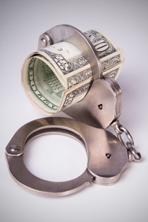 offender: economic crime, the punishment of the offender, roll of dollars in handcuffs, vertical composition, DSLR photography, finance and law, moneys of the United States.