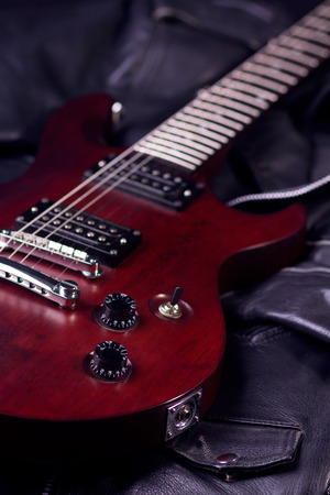 stringed: Electric guitar mahogany, lies on the black leather jackets, vertical composition, a stringed musical instrument, electronic control bodies, six-string guitar.