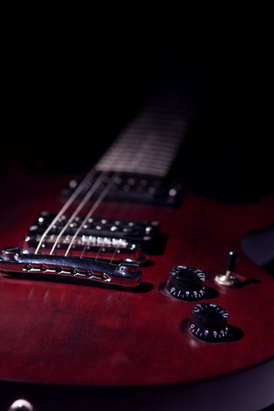 Electric guitar mahogany, dark background, vertical image, a stringed musical instrument, electronic control bodies, six-string guitar, tuning and adjustment. Stock Photo