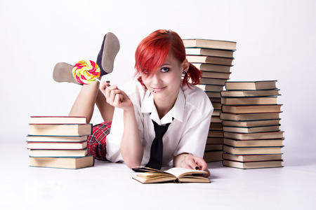 anime eyes: Red-haired girl, style of anime, non-standard, piercings on his face, blue eyes, earrings tunnels, bright lollipop spiral, tie and white shirt, read book, pile of books, student doing homework.