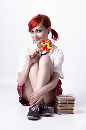 anime eyes: Red-haired girl, image in the style of anime, cheerful face, non-standard, piercings on his face, blue eyes, earrings tunnels, bright lollipop spiral, tie and white shirt, photo in bright colors.