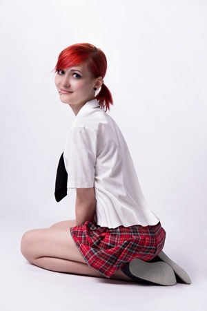 Red-haired girl, style of anime, non-standard, piercings on his face, blue eyes, earrings tunnels, bright lollipop spiral, tie and white shirt, it sits on a white, short skirt, student doing homework.