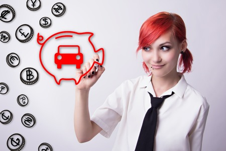 he is different: Red-haired girl, piggy bank for coins, save for a car, banknotes of different countries, should budget, piercings on his face, blue eyes, earrings tunnels, he wrote marker, tie and white shirt. Stock Photo