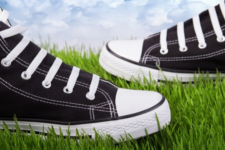 Couple youth sneakers, black and white sneakers, shoes on the green grass, outing, footwear close-up, green lawn, against the sky shoes, shoes for youth, sports shoes on the green grass.