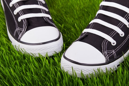 Couple youth sneakers, black and white sneakers, shoes on the green grass, outing, footwear close-up, green lawn, shoes for youth, sports shoes on the green grass.