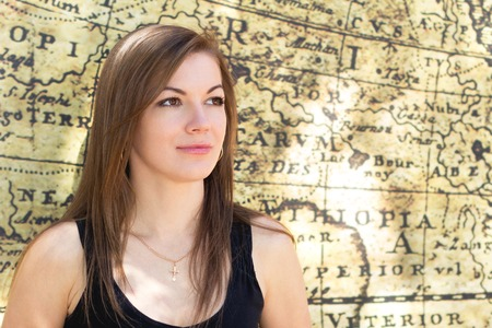 woman pose: Portrait of a young girl, the girl on a walk around town, everyday makeup, old map, long hair, thoughtful look into the distance, jewelry made of gold.