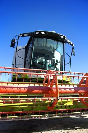 tierra fertil: T�cnicas de cultivo, moderna cosechadora contra el cielo azul, la tierra f�rtil, la producci�n agr�cola, se combinan las cosechas, combine primer plano, equipo para cultivo. Foto de archivo