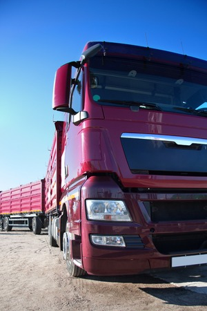 technologically: Heavy tractor with a trailer, trailer for transportation of goods, truck on the sandy road, red truck on background of the sky, the truck carries cargo, trucking cargo on a big lorry Stock Photo