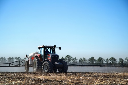 technologically: Tractor watering crops, the farmer drives a tractor, a tractor working in a field, agricultural machinery in operation, the machine sprays the ground