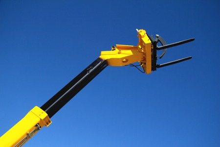 Pointing forklift, boom truck against a blue sky, unloading cargo, hydraulic capture truck, farm equipment, heavy forklift yellow. Stock fotó