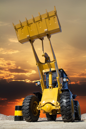 road tractor: Career in the tractor, the tractor at sunset, tractor with big bucket on the sand, transport of building materials, a barrel of fuel and tractors, mining in the quarry, heavy industry. Stock Photo